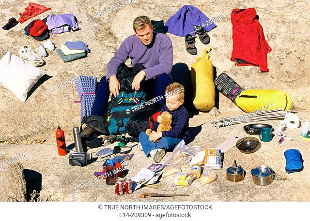 Father and son with camping gear spread out. Utah. USA