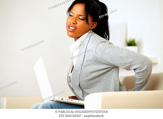 Portrait of a young woman with back pain sits down on sofa at home