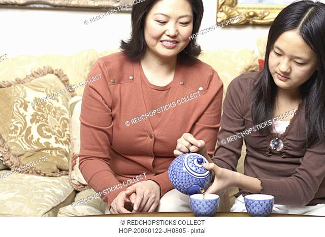 Close-up of a girl pouring tea for her mother