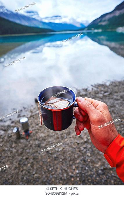 Cropped view of mans hand holding cup of tea by river, Banff, Alberta, Canada