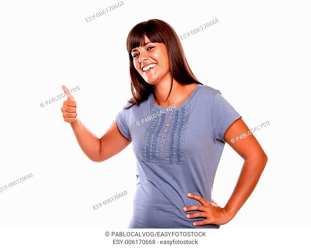 Charming young woman saying good luck on blue shirt while is looking at you on isolated background
