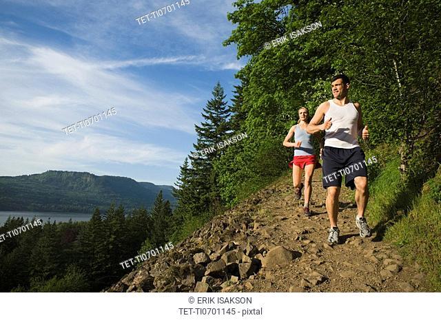 Runners descending rocky trail