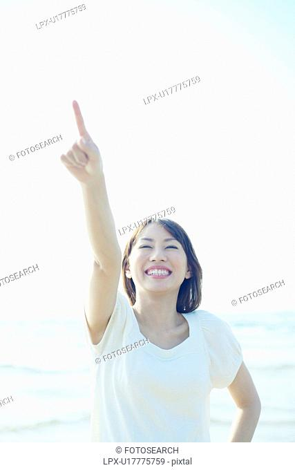 Young Woman Pointing to Sky