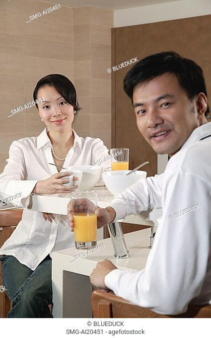 Couple in kitchen having breakfast, looking at camera