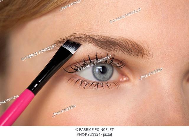 Beautiful woman brushing eyebrow