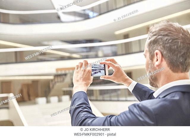 Businessman taking cell phone picture in modern office building