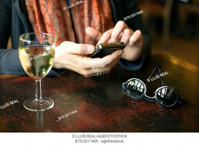 Closeup of woman hands typing a cell phone with a glass of white wine and a pair of sunglasses on the table