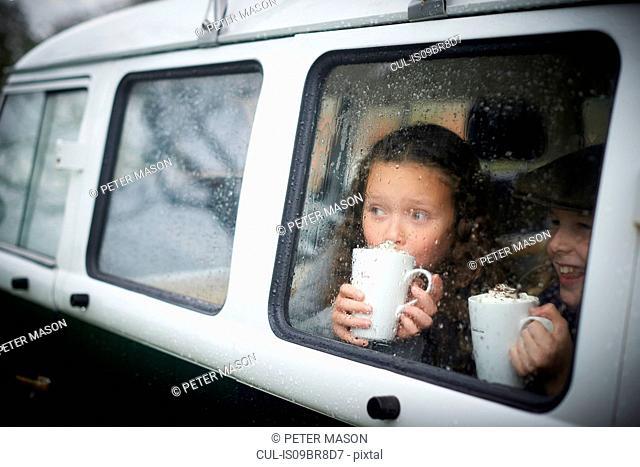 Girls drinking hot chocolate inside camper van
