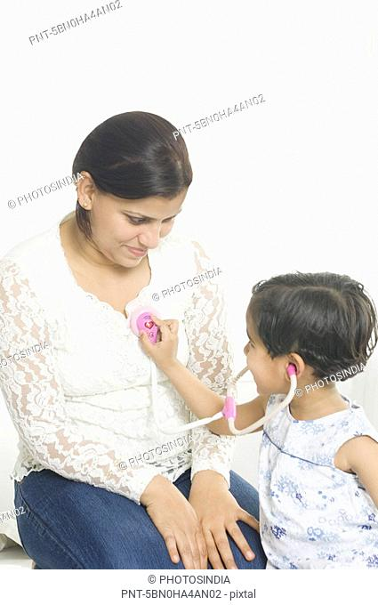 Side profile of a girl examining her mother with a stethoscope and smiling