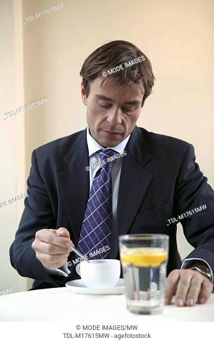A businessman sitting at a table drinking coffee