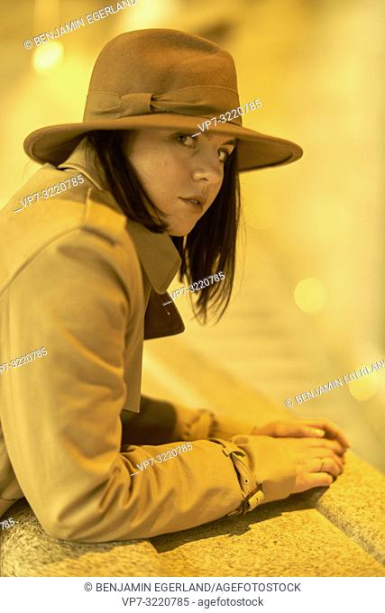 portrait of woman leaning on railing indoors wearing hat, thoughtful pensive emotion, in Munich, Germany