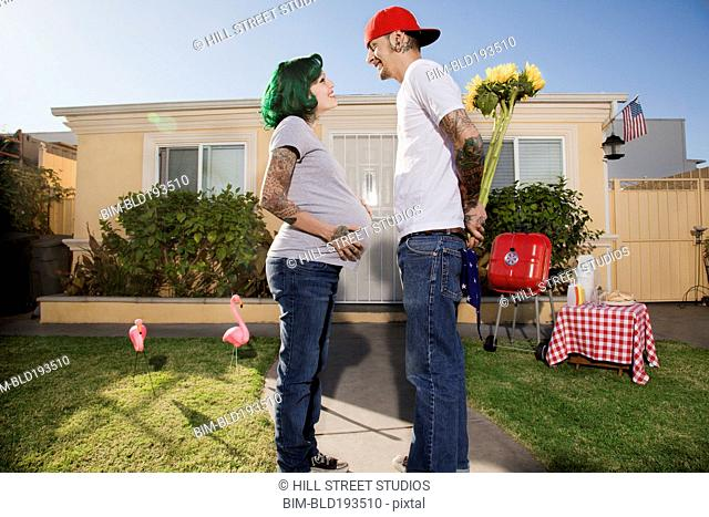 Alternative Hispanic husband giving pregnant wife flowers