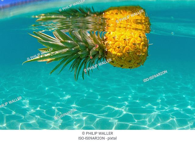 Pineapple floating in swimming pool, close-up