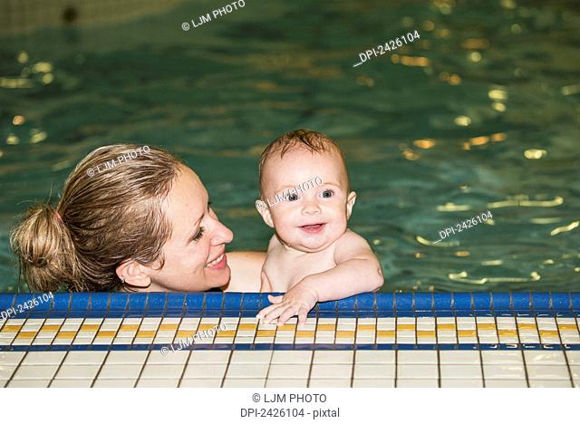 Mother teaching her infant to swim at an indoor pool; St. Albert, Alberta, Canada