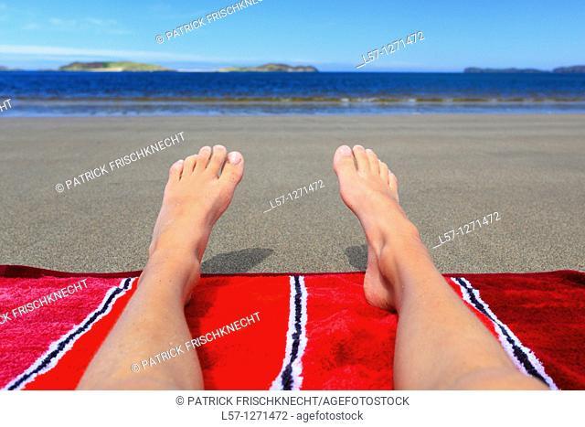boy lying on sandy beach, Sutherland, Scotlandd