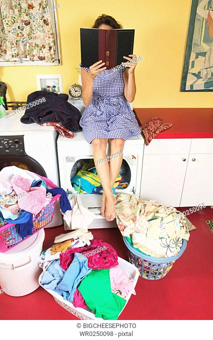 Woman reading instead of doing laundry