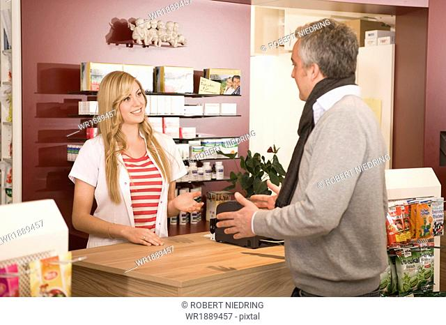 Pharmacist helping customer, Munich, Bavaria, Germany