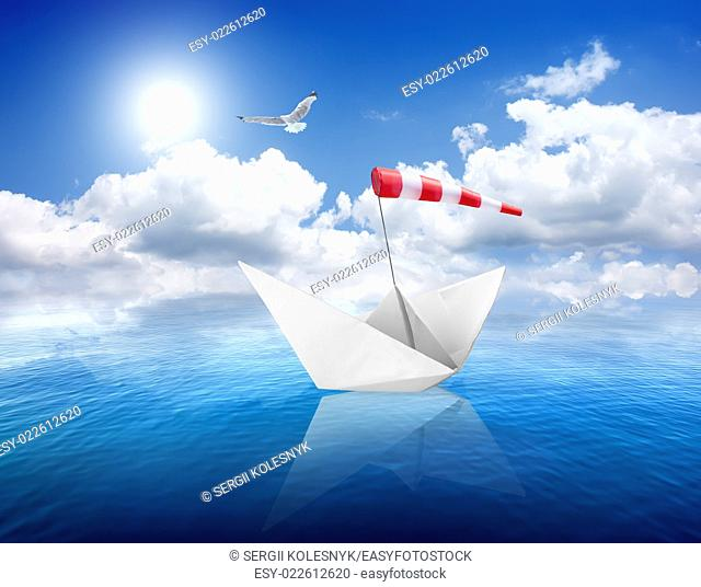 Blue calm sea and the white paper boat