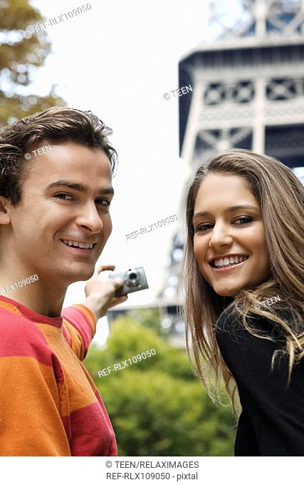 Young couple taking self portrait with Eiffel tower in background, Paris, France