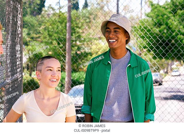 Young man and female friend by park fence, Los Angeles, California, USA