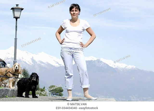 Proud woman standing up with her dogs and snow-capped mountain