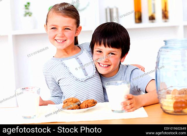Portrait of happy brother and sister eating biscuits