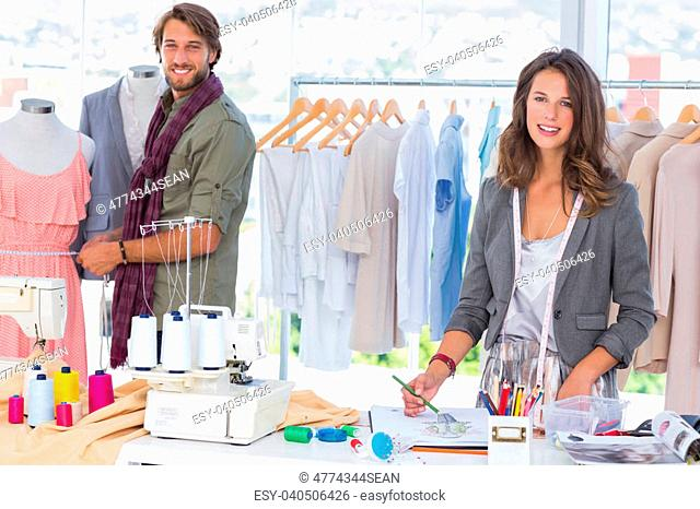 Fashion designers working and smiling at camera in bright office