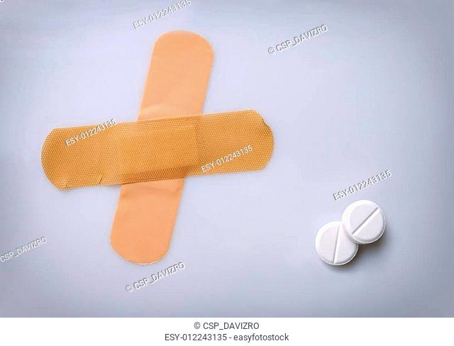 two bandaids and two pills on a table