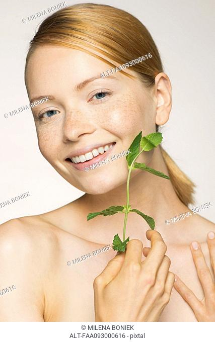 Young woman enjoying softness of fresh mint leaves