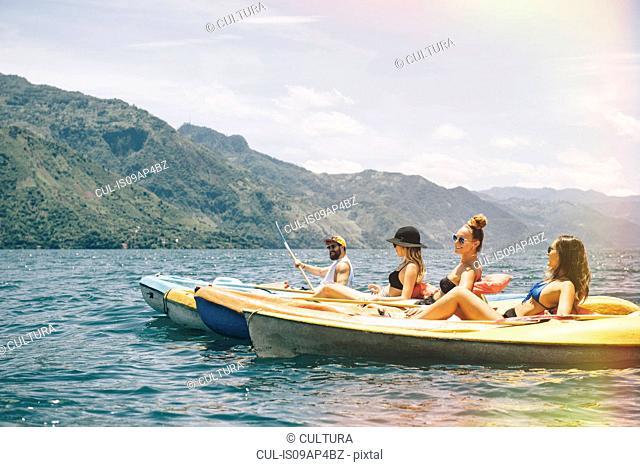 Four young adult friends kayaking on Lake Atitlan, Guatemala