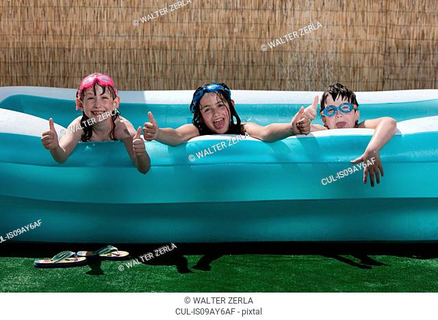 Portrait of two girls and boy giving thumbs up from garden paddling pool
