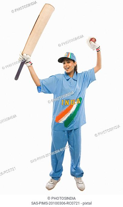 Female cricketer raising bat in celebration