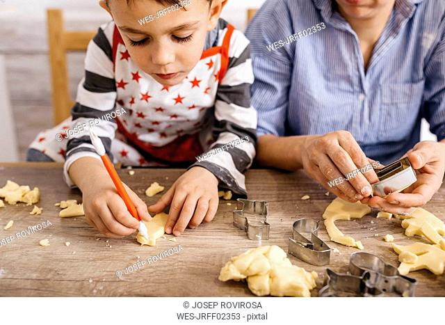 Boy cutting out cookies with tool