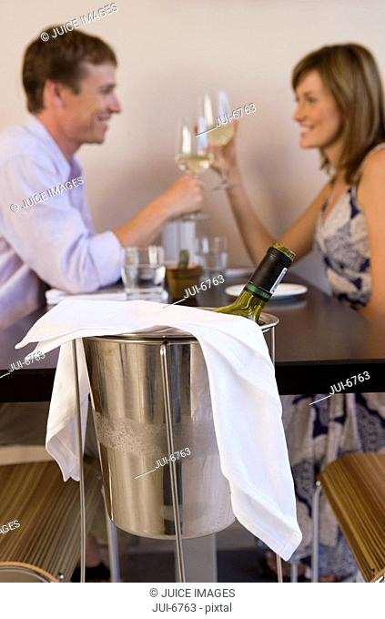 Couple sitting at restaurant table, raising wine glasses in toast, smiling, profile, focus on ice bucket in foreground