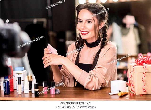 How to apply foundation correctly. Portrait of friendly female model explaining to camera about cosmetology while sitting backstage. She is smiling