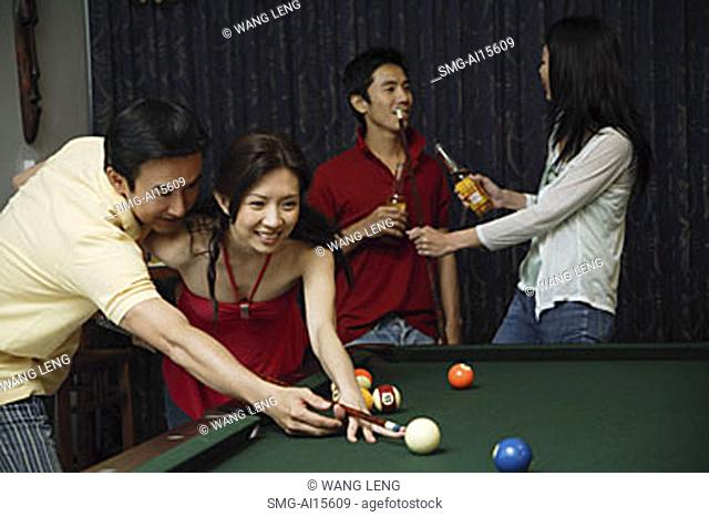 Man teaching woman to play snooker, people in the background
