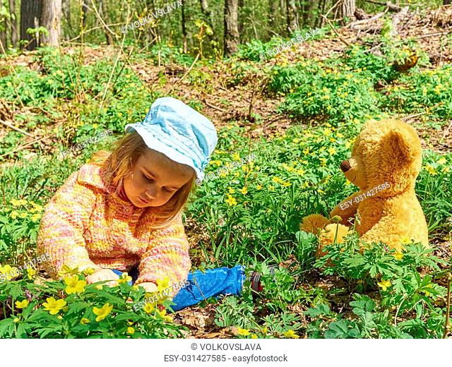 Cute girl playing with an Teddy bear on the grass in forest. Flower meadow