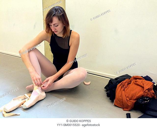Arnhem, Netherlands. Young, female classical ballet dancer tying up het ballet pointers before her training in the ballet studio