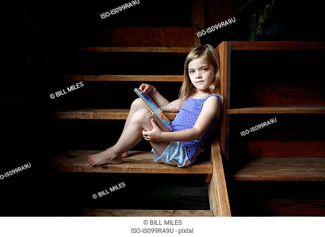 Girl sitting on basement step with digital tablet