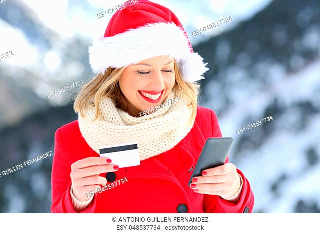 Happy woman wearing santa claus hat paying on line with credit card in christmas with a snowy mountain in the background
