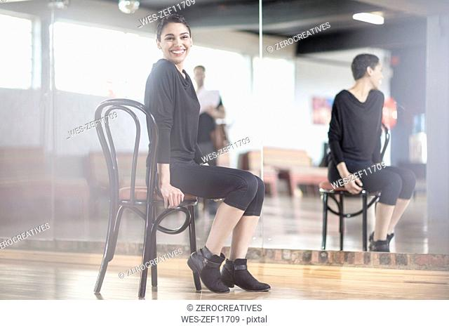 Portrait of smiling female dancer sitting on chair in dance studio