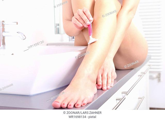 Young woman shaving her legs at washbasin