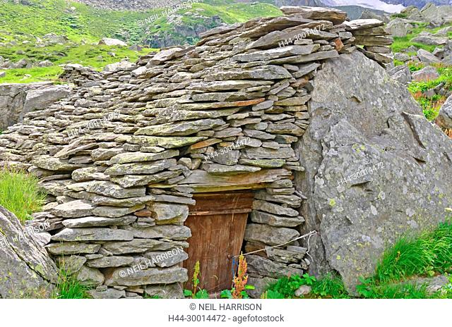 A basic stone shelter in the mountains often used by summer pasture shepherds. Built up against a huge boulder. Italian Alps