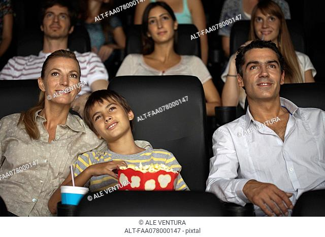 Family enjoying movie in theater, boy resting head on his mother's shoulder