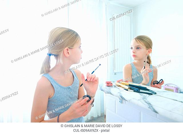 Bedroom mirror image of girl with make up brush staring at herself