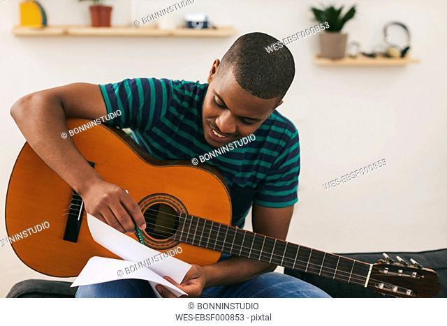 Smiling man with guitar writing down something