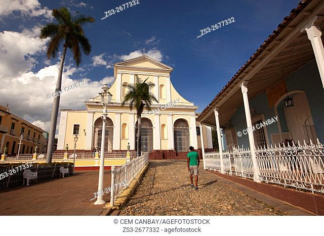 Man in front of the Iglesia de Santisima Trinidad in Plaza Mayor-Main Square, Trinidad, Sancti Spiritu Province, Cuba, West Indies, Central America