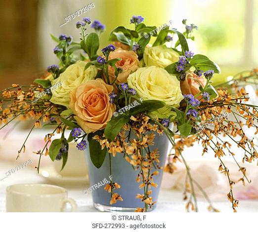 Vase of roses with forget-me-nots and broom