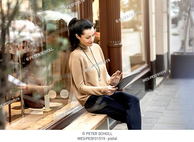 Mature woman sitting in front of her fashion store, using tablet