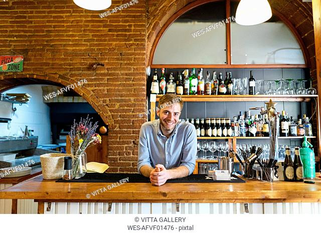 Portrait of smiling man leaning on counter of a pizzeria